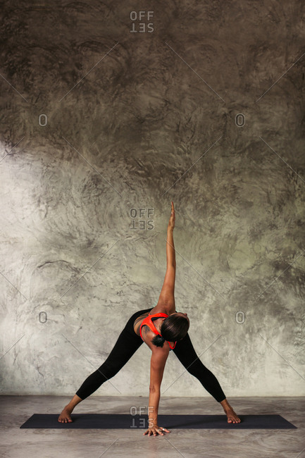 Woman standing in a straddle yoga pose with one arm raised upward