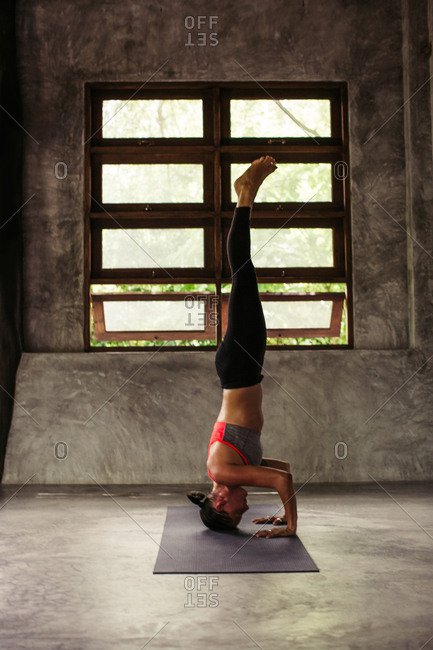 Woman performing a headstand yoga pose in an industrial studio