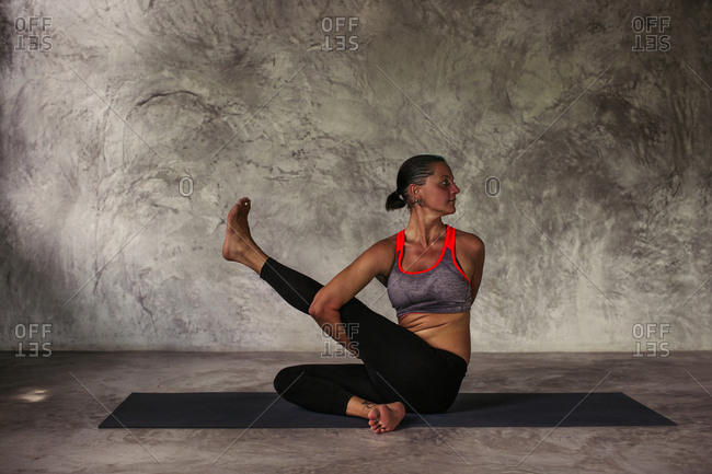 Woman in a seated yoga position crossing one raised leg in front of her body