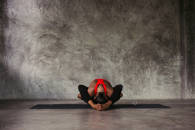 Woman in a seated yoga position clasping her hands beneath her legs behind her