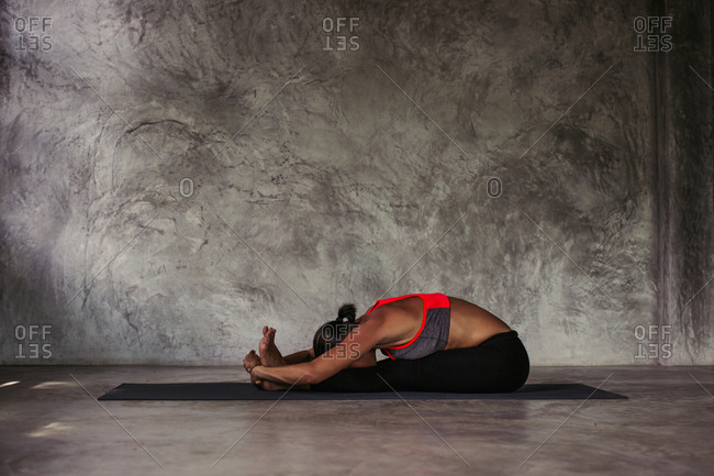 Woman practicing a seated forward fold yoga position