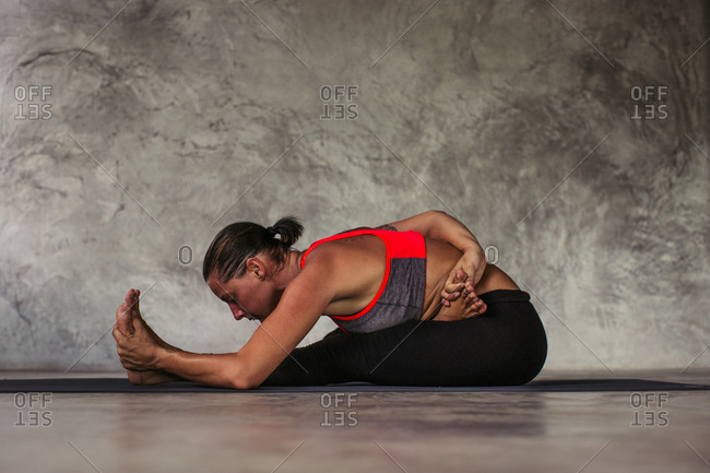 Woman in a seated yoga position reaching behind her back to clasp her foot