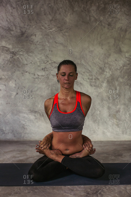 Woman in a lotus yoga position clasping opposing feet with her hands behind her back