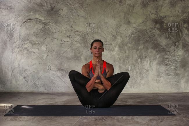 Woman In A Flowering Lotus Yoga Pose With Her Hands Clasped Together