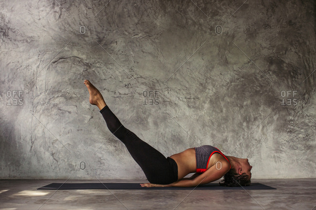 Woman performing a fish yoga pose with her legs raised straight up
