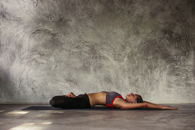 Woman practicing a yoga pose lying on her back with legs crossed