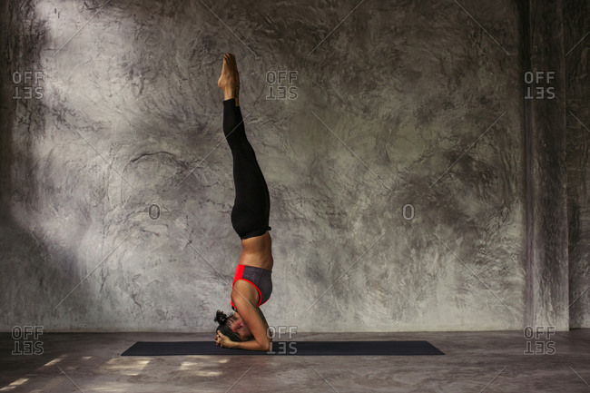 Woman in a headstand yoga pose with her legs stretched straight into the air