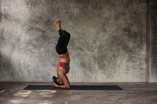 Woman in a headstand yoga pose with the soles of her feet touched together