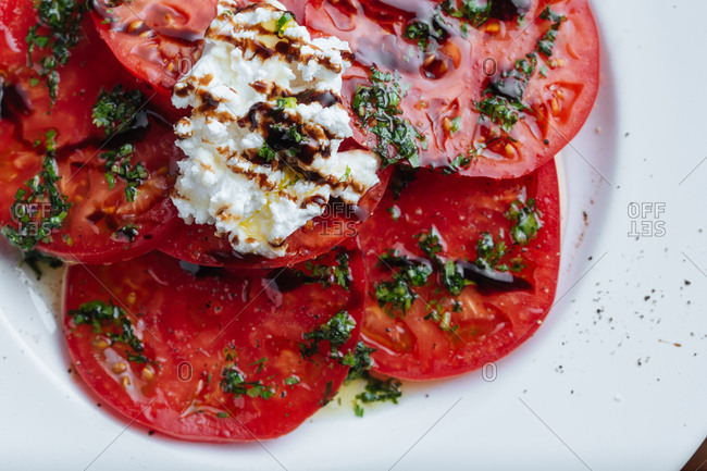 Plate of sliced tomatoes with ricotta cheese