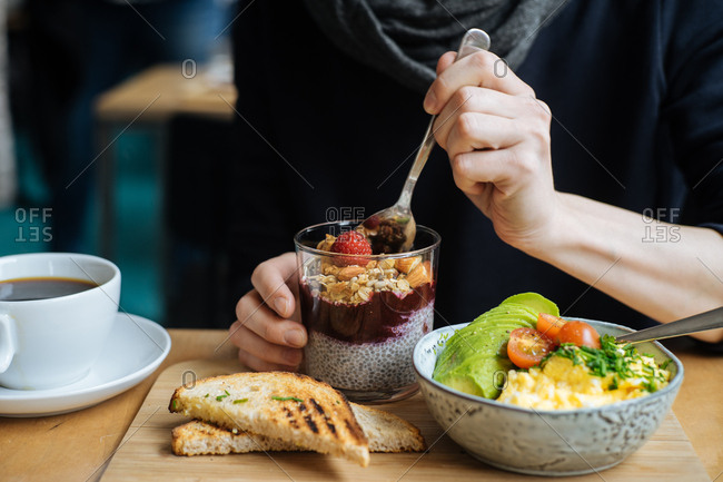 Woman with hearty breakfast of chia pudding and eggs with avocado