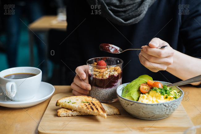 Woman eating chia pudding with fruit at breakfast table