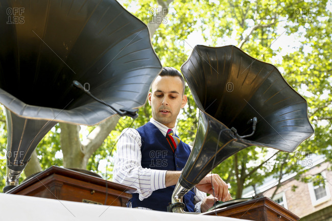 New York City, United States - June 10, 2017: 1920's Jazz Age Lawn Party at Governors Island, Man playing music on a vintage phonograph at a party