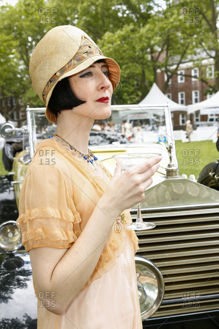 New York City, United States - June 10, 2017: 1920's Jazz Age Lawn Party at Governors Island, Woman dressed as a flapper drinking a martini at a garden party