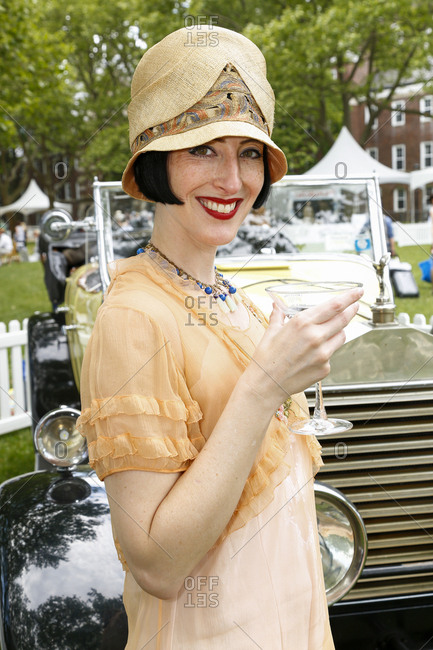 New York City, United States - June 10, 2017: 1920's Jazz Age Lawn Party at Governors Island, Woman dressed as a flapper holding a martini glass and smiling