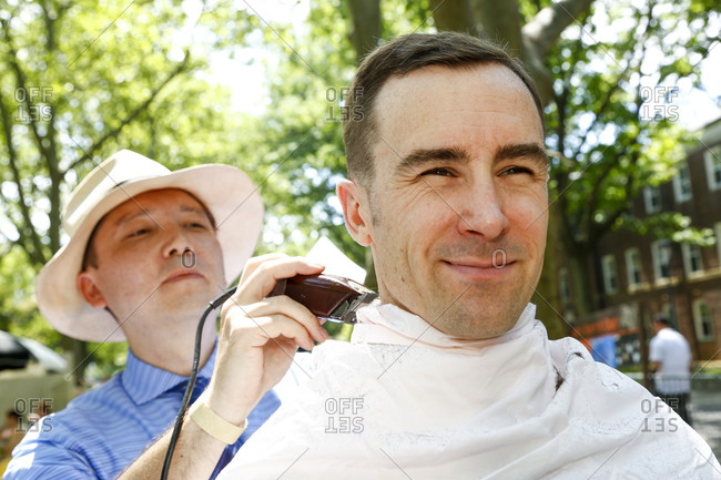 New York City, United States - June 10, 2017: 1920's Jazz Age Lawn Party at Governors Island, Man getting an old-fashioned haircut at a garden party