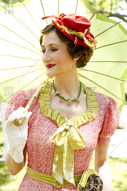 New York City, United States - June 10, 2017: 1920's Jazz Age Lawn Party at Governors Island, Woman in a vintage hat and dress holding an umbrella