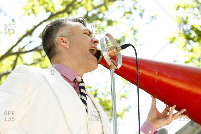 New York City, United States - June 10, 2017: 1920's Jazz Age Lawn Party at Governors Island, Musician singing into a megaphone and vintage microphone