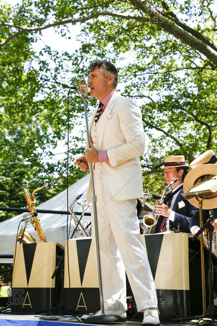 New York City, United States - June 10, 2017: 1920's Jazz Age Lawn Party at Governors Island, Band leader singing into a microphone at a garden party