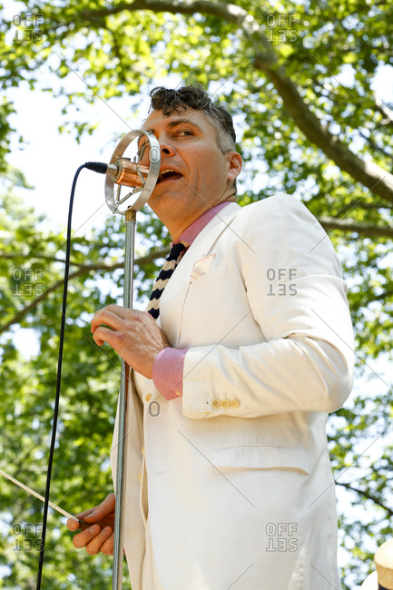 New York City, United States - June 10, 2017: 1920's Jazz Age Lawn Party at Governors Island, Musician singing into a vintage microphone at a garden party