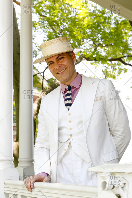New York City, United States - June 10, 2017: 1920's Jazz Age Lawn Party at Governors Island, Man in an all-white vintage suit standing on a porch at a 1920s-themed party