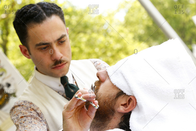 New York City, United States - June 10, 2017: 1920's Jazz Age Lawn Party at Governors Island, Barber in vintage clothing trimming a customer's beard