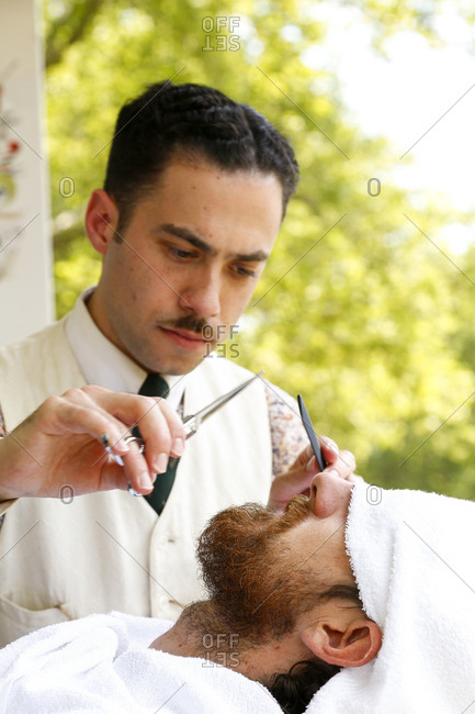 New York City, United States - June 10, 2017: 1920's Jazz Age Lawn Party at Governors Island, Barber grooming a man's beard at a 1920s-themed party