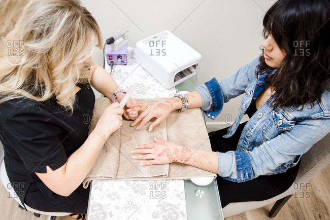 Woman receiving a manicure in salon