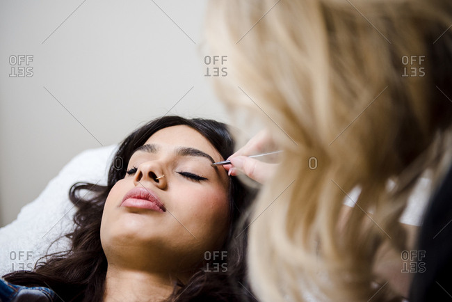 Woman receiving brow treatment in salon