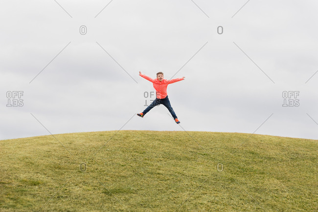 Boy on hilltop leaping into air