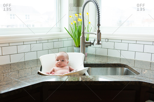 Baby in bathing seat in sink