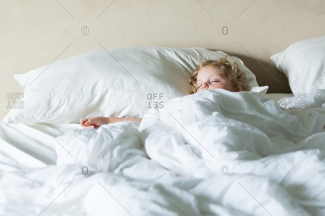 Girl nestled in cozy bed