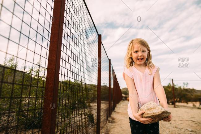 Little girl holding a big rock