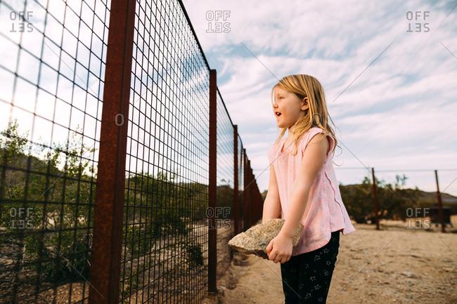 Girl holding a heavy rock