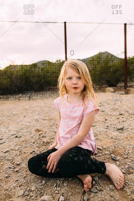 Girl sitting on ground in yard next to desert