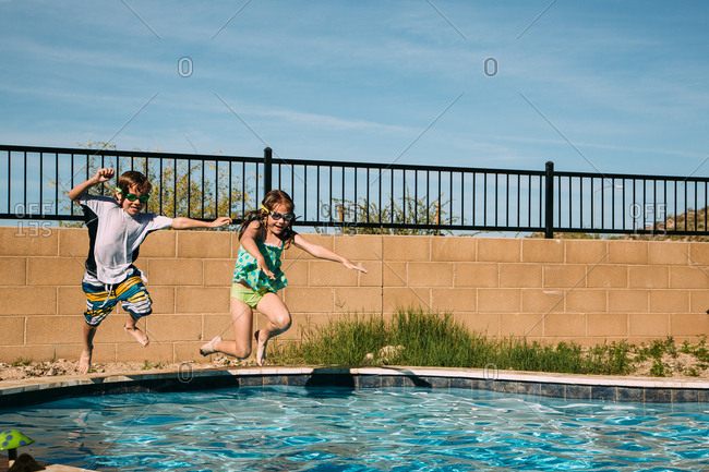 Girl and boy jumping into swimming pool at the same time
