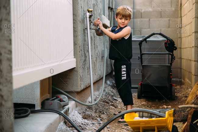 Boy using hose to fill toy truck with water