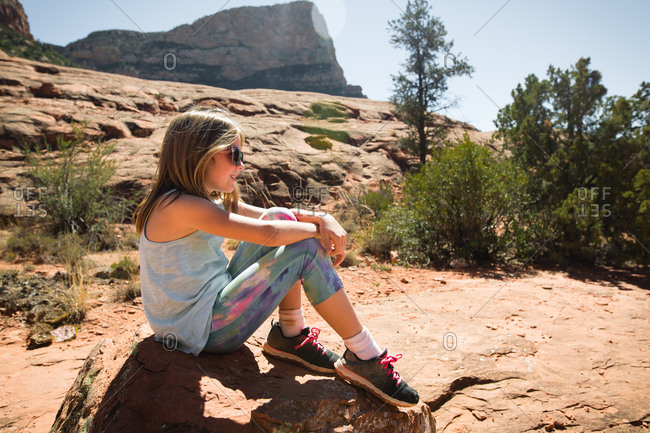 Girl sitting on a rock in natural desert environment