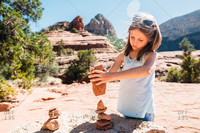 Girl balancing a stack of rocks in the desert