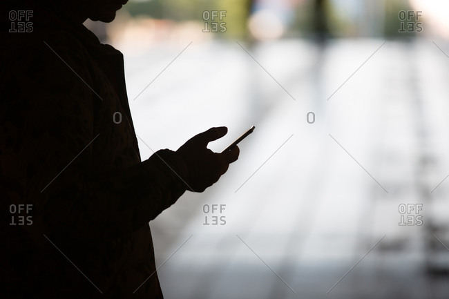 Silhouette of man messaging on mobile phone