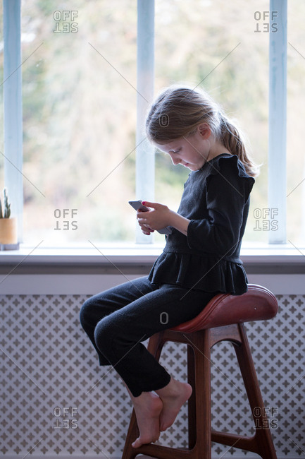 Girl sitting on stool and messaging on mobile phone
