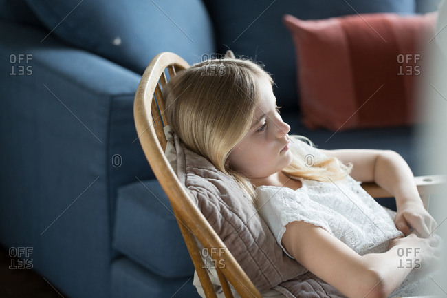 Thoughtful girl relaxing on wooden chair at home