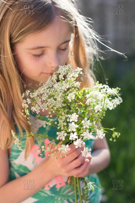 Cute girl smelling bouquet of fresh yarrow flowers
