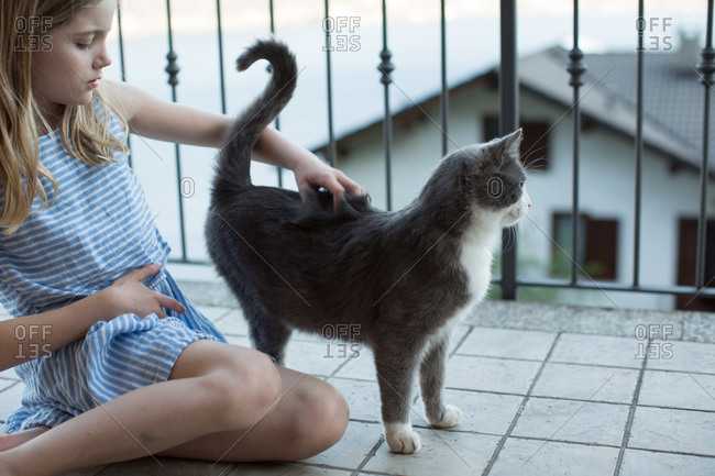 Girl petting cat on porch