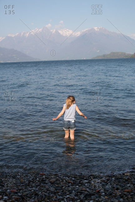 Rear view of girl standing in sea water