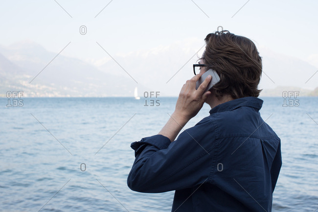 Man talking on mobile phone by sea