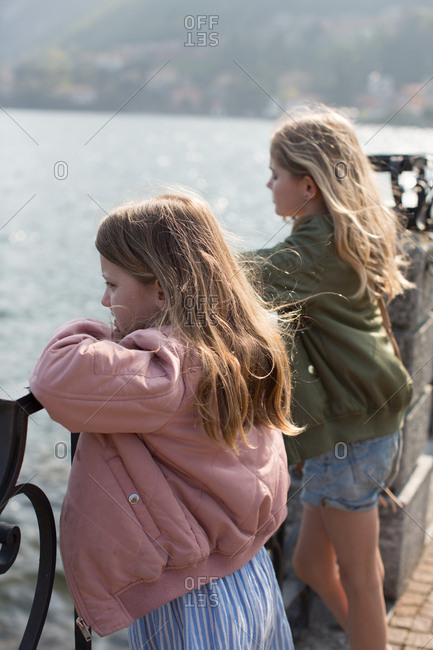 Girls admiring seascape from fence