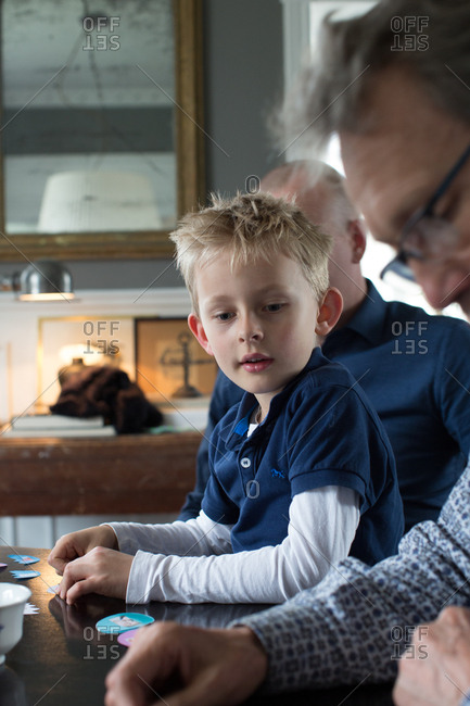 Boy playing game with grandfather on table