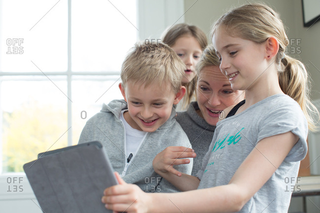 Mother with children having fun while watching digital tablet at home