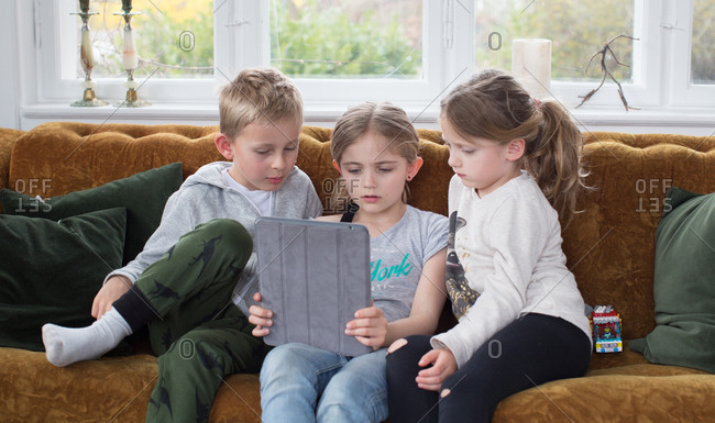 Brother and sisters using digital tablet on sofa