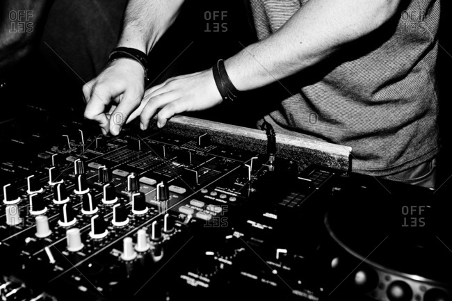 A disc jockey or DJ is performing a live show in a nightclub.